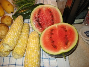 Watermelon next to peeled corn