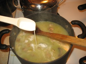 spooning heavy cream into the soup