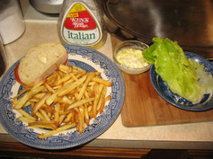 Entire meal: fries with relish sauce, sandwich, lettuce with Italian dressing