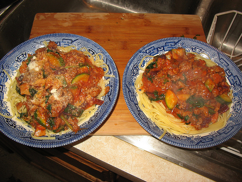 Two bowls of pasta heaping with a meat and veggie filled sauce
